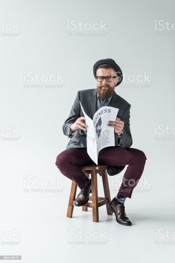 Businessman with vintage mustache and beard reading business newspaper while sitting on stool - Zbiór zdjęć royalty-free (Biznes)