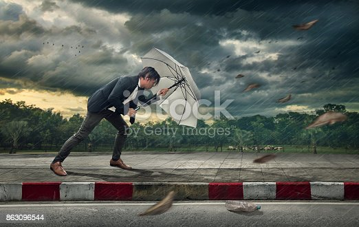 istock Businessman with white umbrella protecting himself from the storm.  Business heavy tasks and problems concept. 863096544