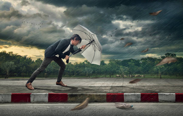 businessman with white umbrella protecting himself from the storm.  business heavy tasks and problems concept. - conquering adversity stock photos and pictures