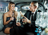 Businessman with young woman in a limousine.