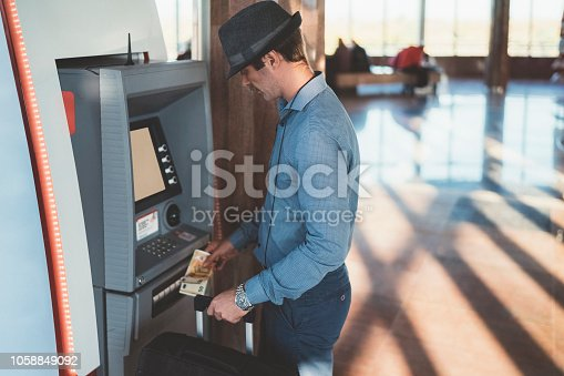 istock Businessman withdrawing money from ATM on airport 1058849092