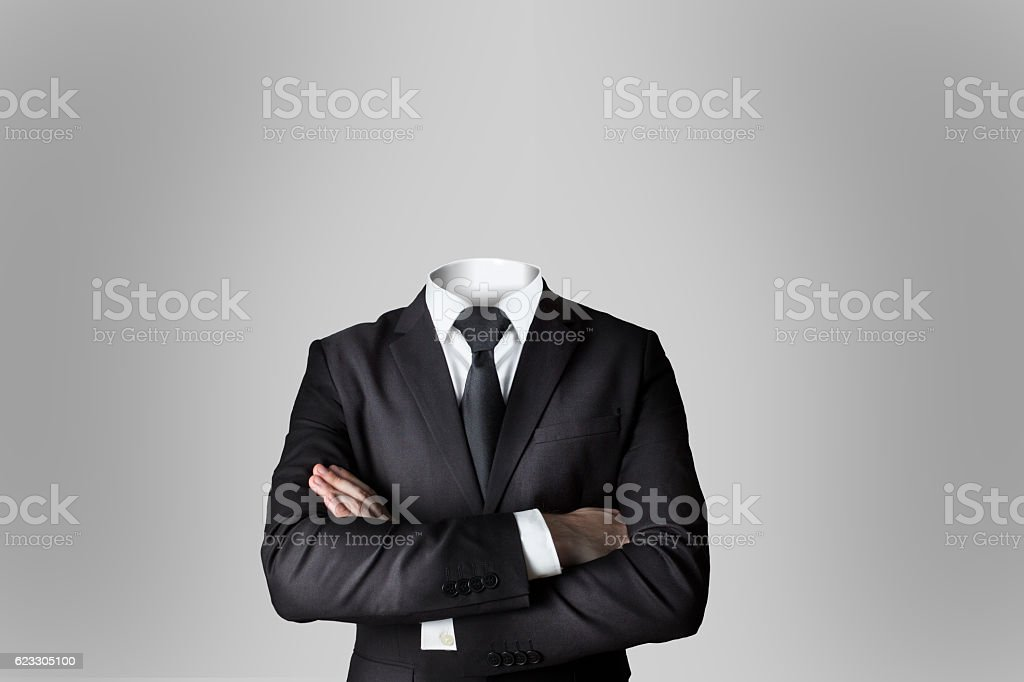 businessman without head crossed arms grey background stock photo