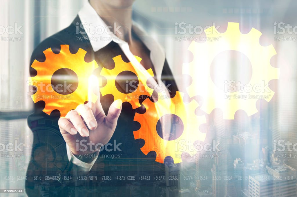 Businessman women toching the screen of the mechanical gear stock photo