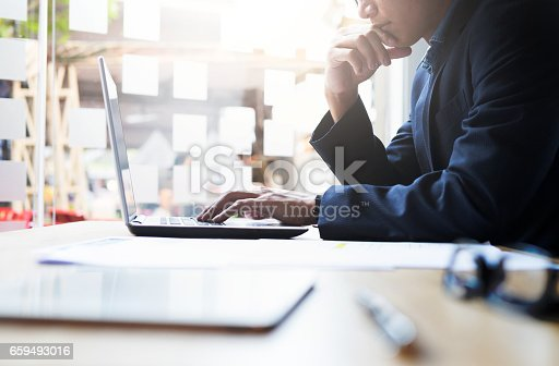 Startup businessman working analysis business information at office with laptop and documents on his desk.