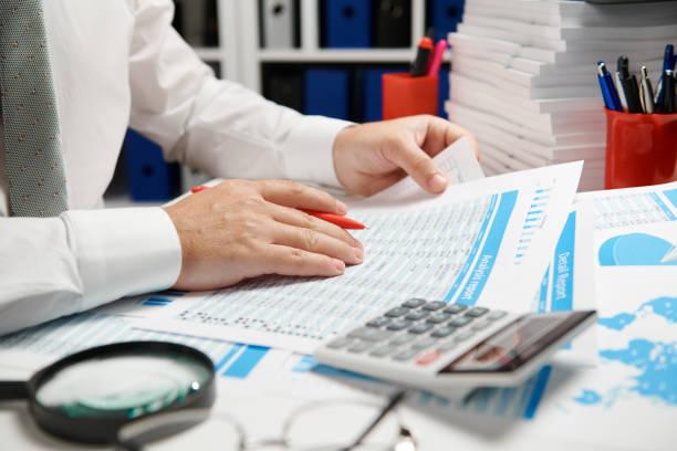 geschäftsmann arbeitet und berechnet, liest und schreibt berichte. büromitarbeiter, tabellennahaufnahme. business financial accounting konzept. - lesen arbeitsblätter stock-fotos und bilder