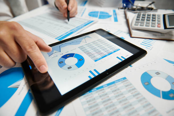 Empresario trabajando y calculando, lee y escribe informes. Uso de tablet pc. Empleado de la oficina, primer plano de mesa. Concepto de contabilidad financiera empresarial. - foto de stock