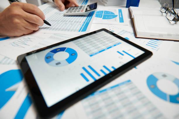 geschäftsmann arbeitet und berechnet, liest und schreibt berichte. mit tablet-pc. büromitarbeiter, tabellennahaufnahme. business financial accounting konzept. - lesen arbeitsblätter stock-fotos und bilder