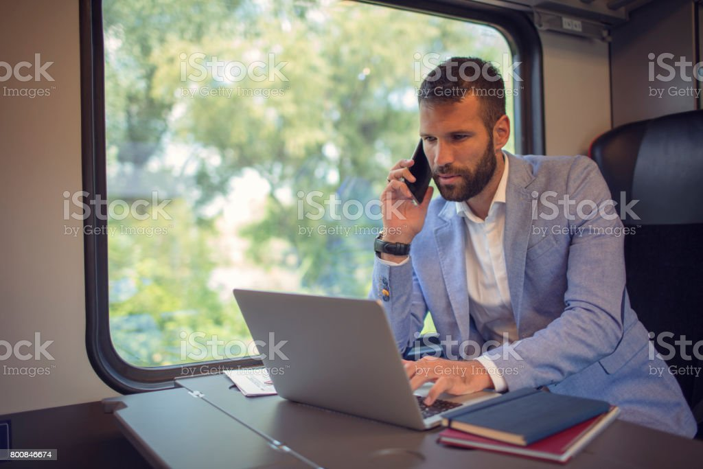 Businessman working and traveling by train stock photo