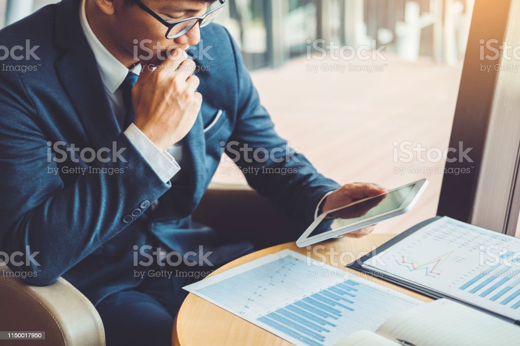 Businessman working and using Digital Tablet new business project finance investment at coffee cafe. Businessman working and using Digital Tablet new business project finance investment at coffee cafe. Business Stock Photo
