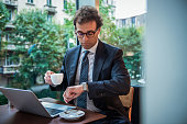 An elegant businessman drinks coffee in a cafe, uses a laptop and checks his watch