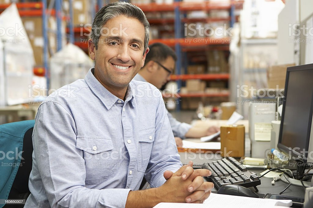 Businessman Working At Desk In Warehouse stock photo