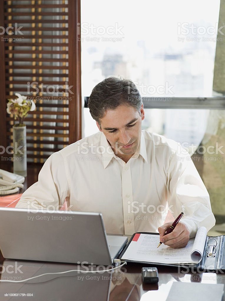 Businessman working at desk, smiling foto stock royalty-free