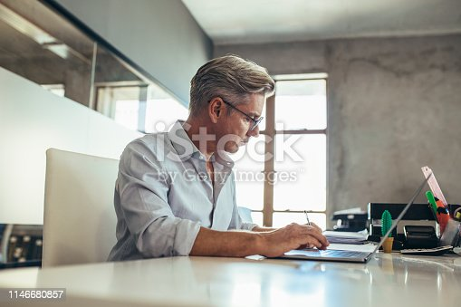 Mature businessman working at his desk. Male executive making notes while working on laptop in office.