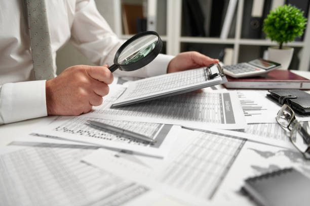 geschäftsmann arbeitet im büro und berechnet finanzen, liest und schreibt berichte. konzept der business financial accounting. - lesen arbeitsblätter stock-fotos und bilder