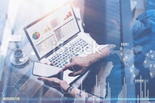 474953508 istock photo Businessman working at office on laptop.Man holding smartphone in hands.Concept of digital screen,virtual connection icon,diagram,graph interfaces on background.Double exposure. 855069726