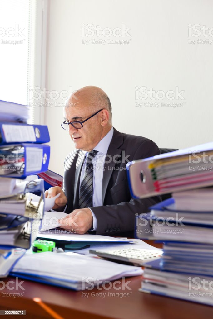 Businessman working at the desk inside the files royalty-free stock photo
