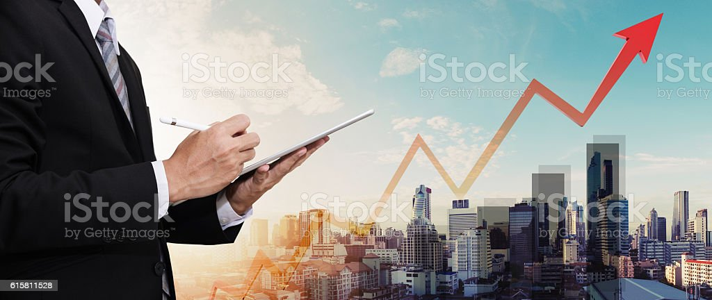 Businessman working digital tablet, with panorama city and raising arrow stock photo