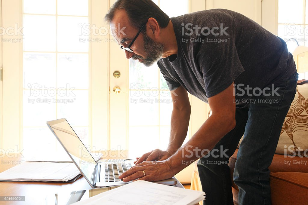 Businessman Working From Home Bends Over To Look At Laptop stock photo