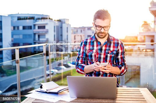 istock Businessman working from home on laptop, standing on balcony 540574728