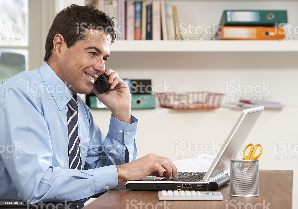 Businessman working from home using laptop and phone  royalty-free stock photo