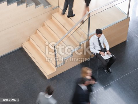 483635979 istock photo Businessman working in busy office corridor 483635973