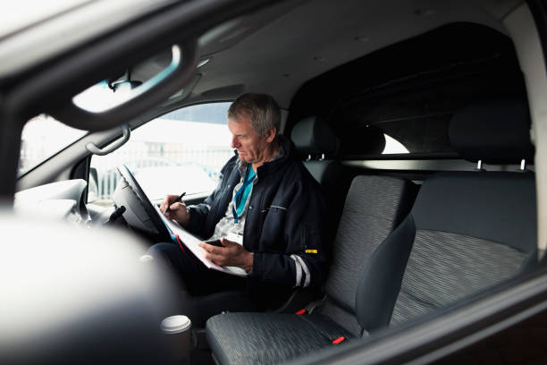 Businessman Working In Car Businessman is working in the driver seat of his car while stationary. He is filling in paperwork and holding a smart phone. driving instructor stock pictures, royalty-free photos & images