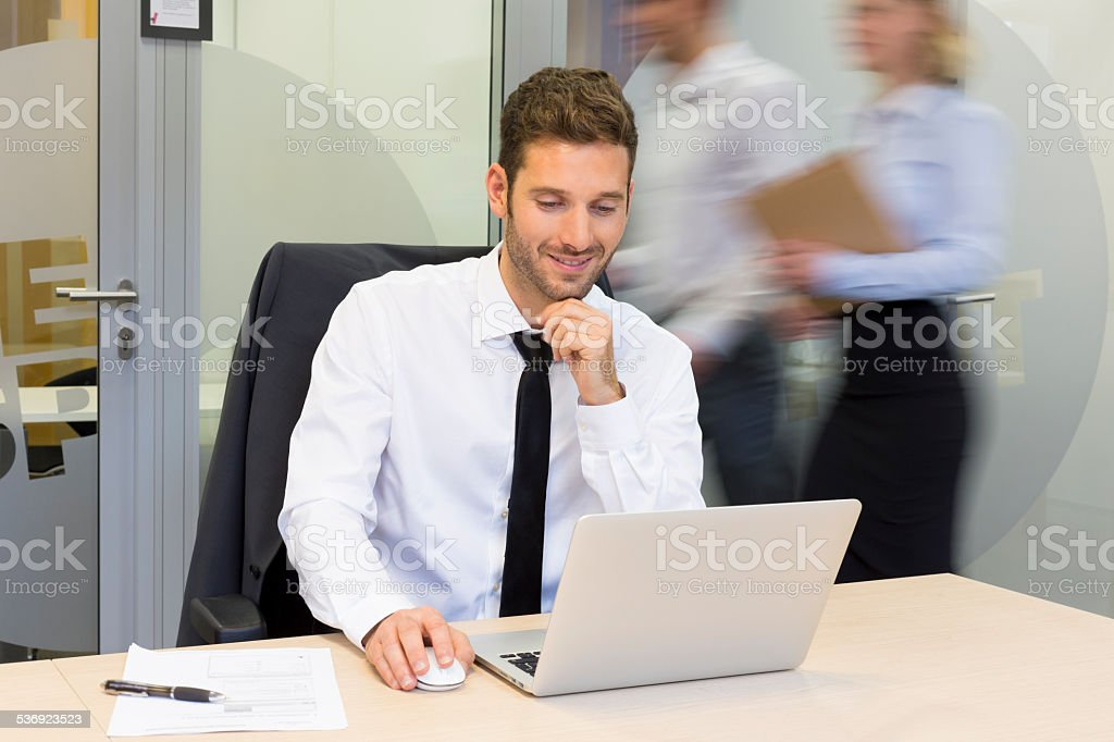 Businessman working in office, business peoples moving behind him royalty-free stock photo