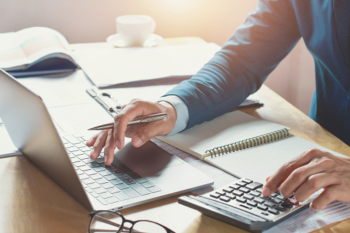 istock businessman working in office with using calculator and laptop. concept finance and accounting 942682414