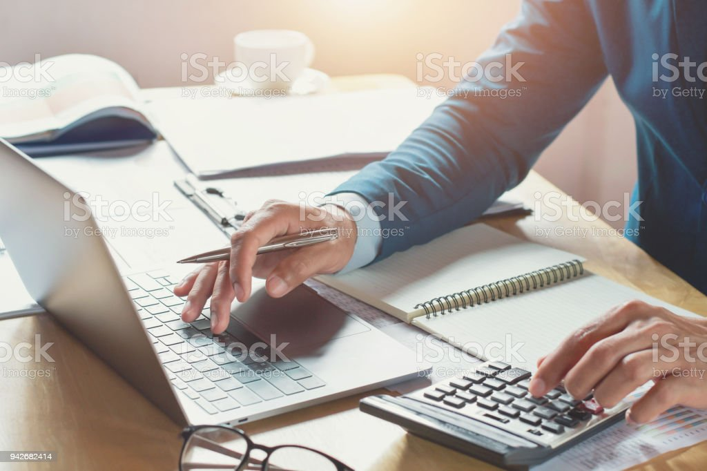 businessman working in office with using calculator and laptop. concept finance and accounting stock photo