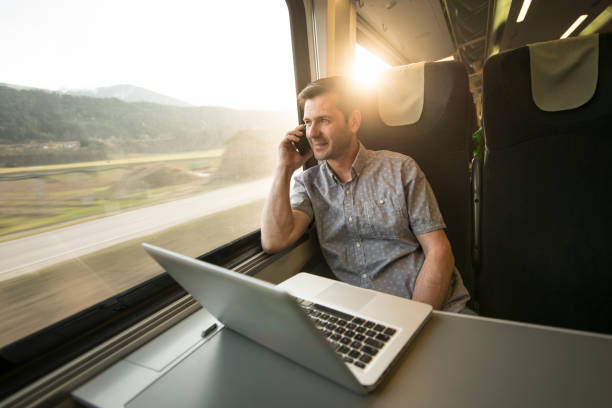 homme d'affaires travaillant mobiles au cours de voyages en train - train photos et images de collection