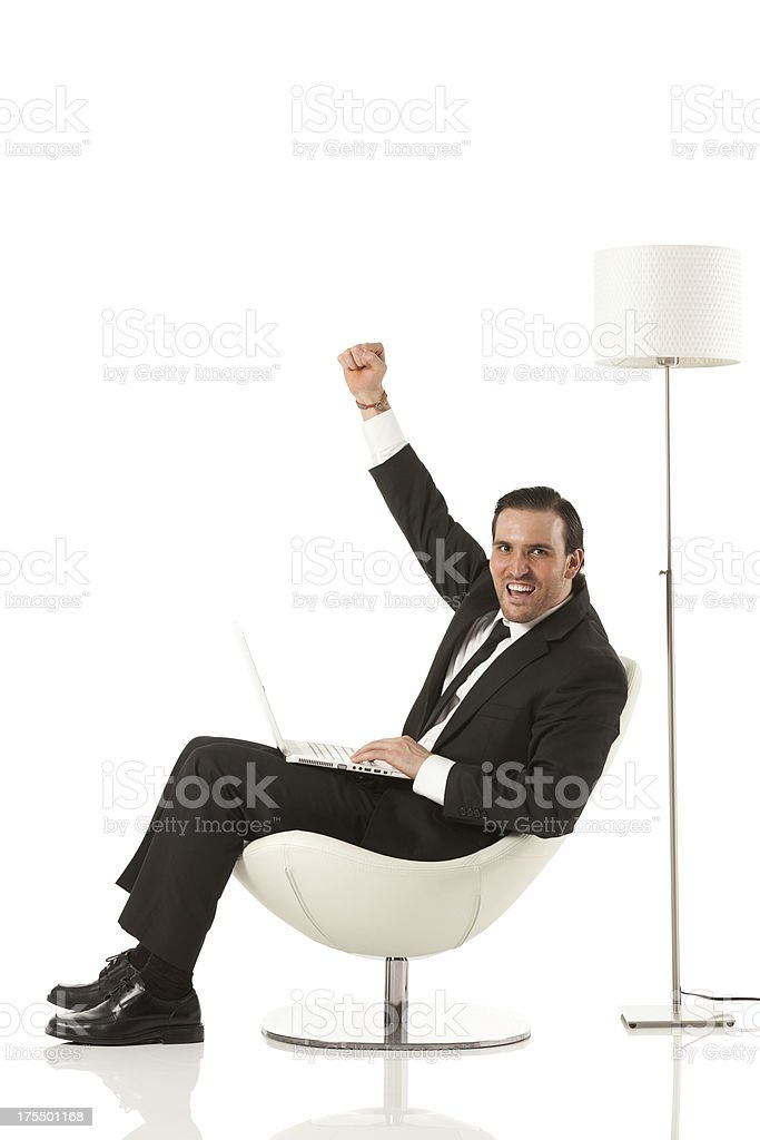 Businessman working on a laptop and cheering stock photo