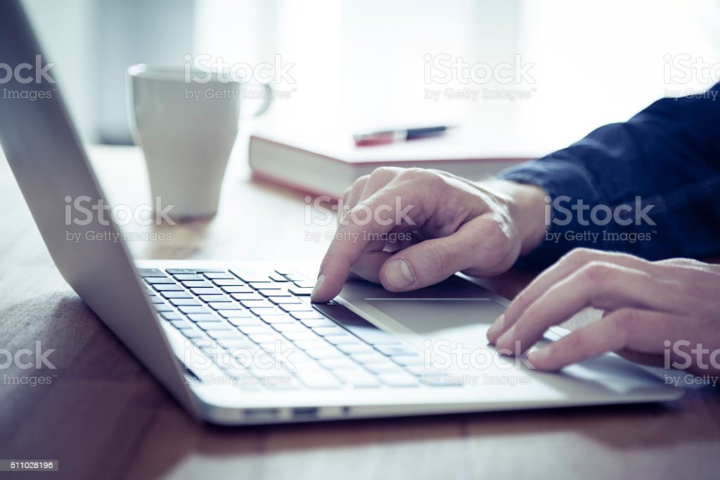 Businessman Working on a Laptop from Home or Hotel stock photo