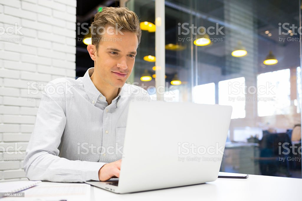 Businessman working on a light colored laptop at the office stock photo