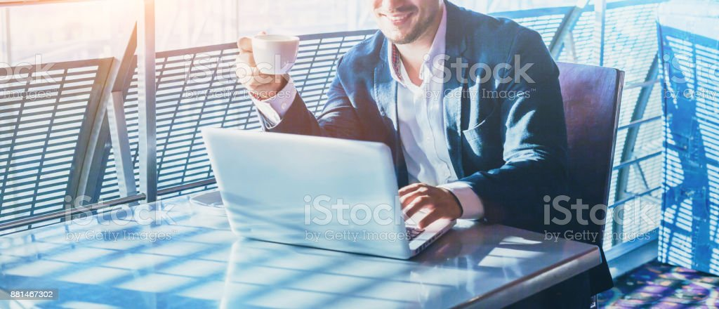 businessman working on computer, drinking coffee and smiling stock photo