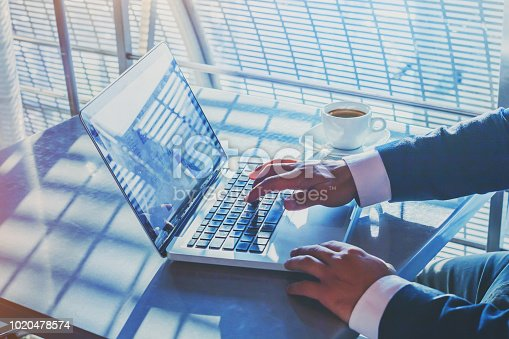 879813798istockphoto businessman working on computer in airport, banking online 1020478574