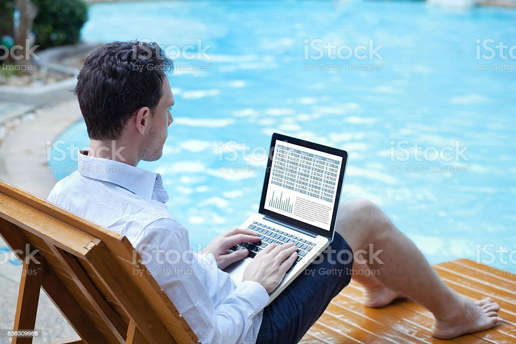 businessman working on computer on the beach stock photo