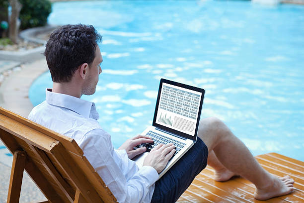 businessman working on computer on the beach - lesen arbeitsblätter stock-fotos und bilder