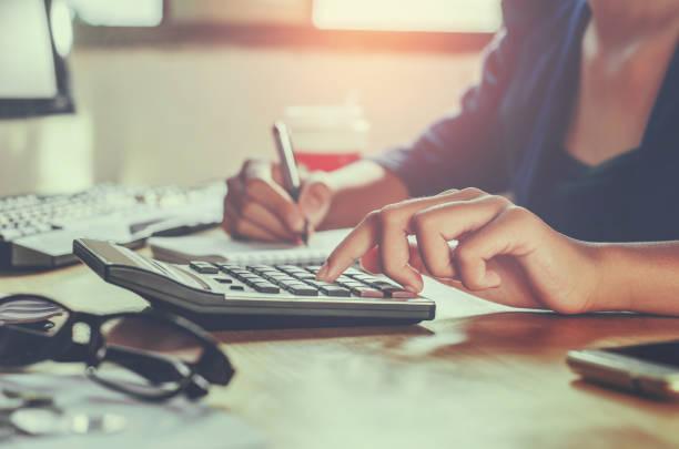 geschäftsmann, arbeiten am schreibtisch büro mit taschenrechner geschäftskonzept finanz-rechnungswesen - gehaltsstreifen stock-fotos und bilder