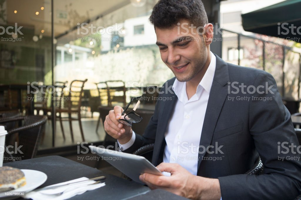Businessman working on digital tablet in cafe. stock photo