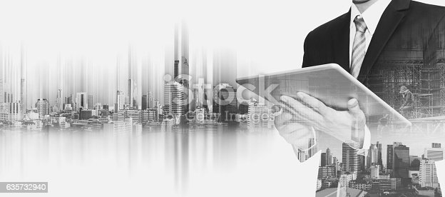 635942136istockphoto Businessman working on digital tablet, with double exposure city 635732940