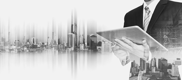 635942136 istock photo Businessman working on digital tablet, with double exposure city 635732940