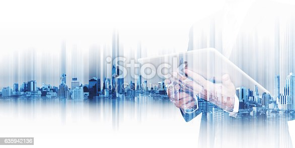 istock Businessman working on digital tablet, with double exposure city background 635942136