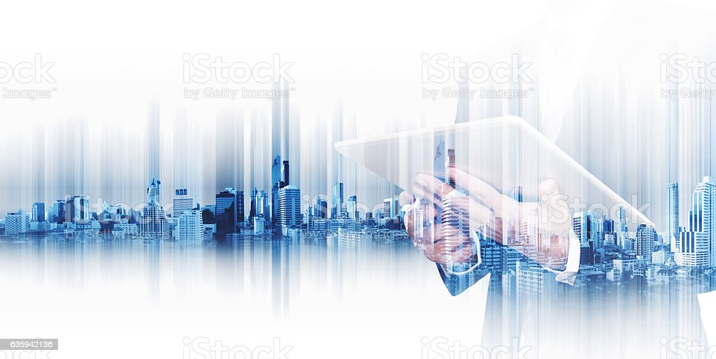 Businessman working on digital tablet, with double exposure city background stock photo