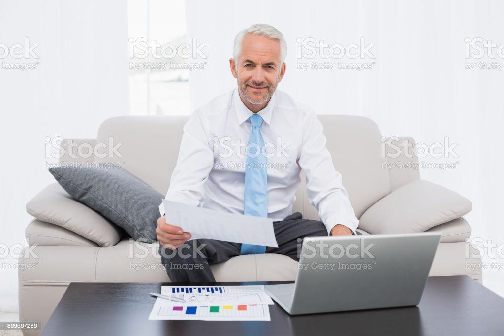 Homem de negócios trabalhando em gráficos e laptop em casa - foto de acervo