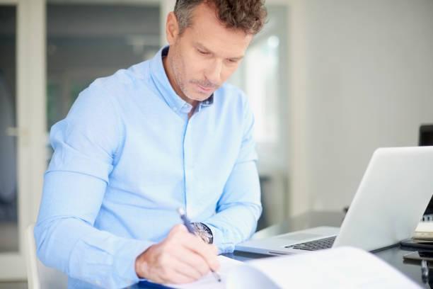 Geschäftsmann am Laptop arbeiten und dabei einige Papiere – Foto