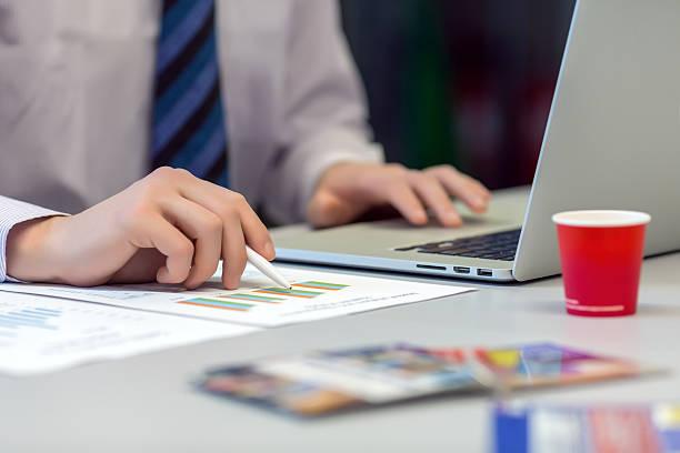 geschäftsmann arbeiten mit laptop und bedruckte diagramme - lesen arbeitsblätter stock-fotos und bilder