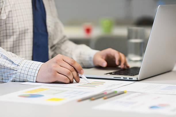 Geschäftsmann arbeiten mit Laptop und bedruckte Diagramme – Foto