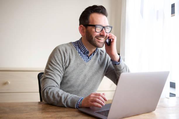 zakenman die op laptop werkt en praten op mobiele telefoon - mid volwassen mannen stockfoto's en -beelden