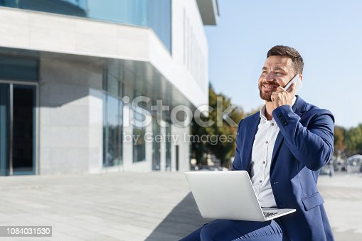 istock Businessman working on laptop and talking on phone outdoor 1084031530
