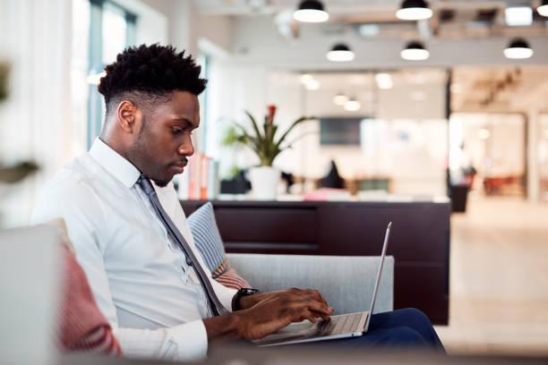在共用工作區辦公室的辦公桌上使用筆記本電腦的商人 - 虛擬辦公室 個照片及圖片檔